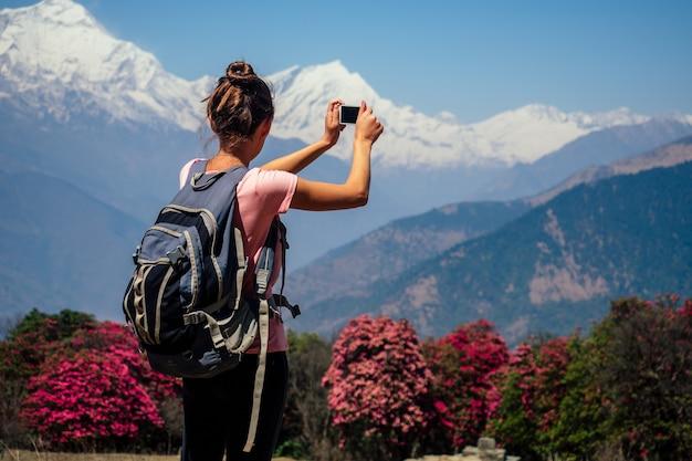 Молодая туристка с походным рюкзаком фотографирует пейзажи и делает селфи в гималаях. концепция треккинга в горах
