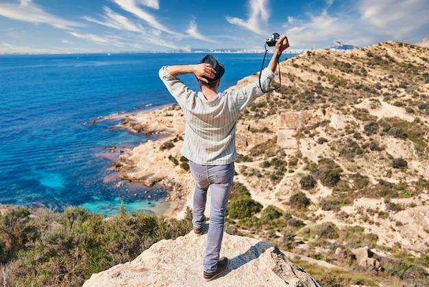 젊은 여행자가 바다가 보이는 언덕 위에 자유의 상징으로 팔을 들고