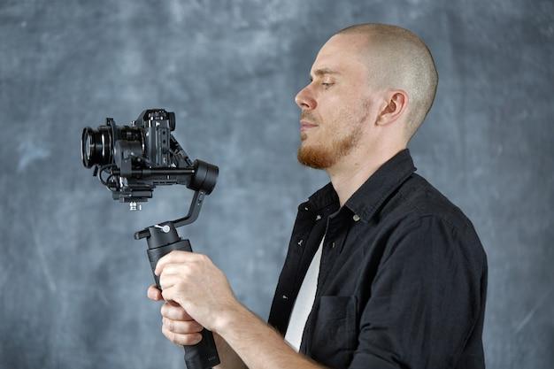 검은 셔츠를 입은 젊은 비디오그래퍼가 3축 안정기에 전문 카메라를 들고 있다