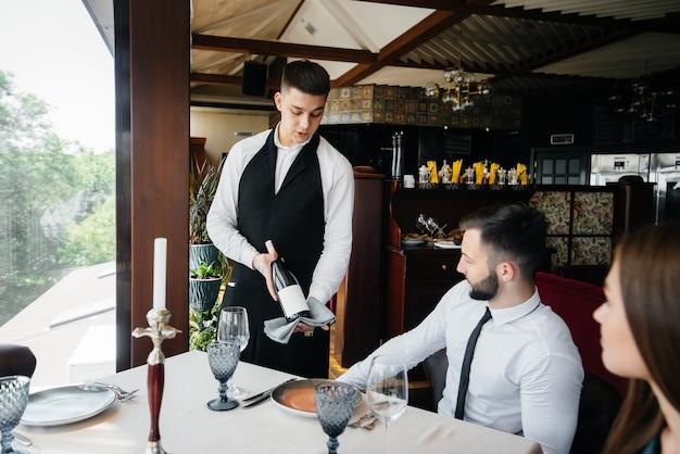세련된 앞치마를 입은 젊은 웨이터가 레스토랑에서 아름다운 커플에게 고급 와인을 시연하고 제공합니다. 고객 서비스.