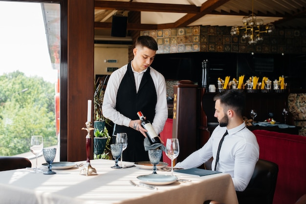 세련된 앞치마를 입은 젊은 웨이터가 레스토랑에서 고객에게 고급 와인을 시연하고 제공합니다. 고객 서비스.