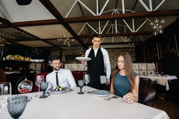 세련된 앞치마를 입은 젊은 웨이터가 세련된 레스토랑에서 아름다운 부부와 함께 테이블을 제공합니다. 고객 서비스.