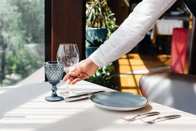세련된 유니폼을 입은 젊은 웨이터가 아름다운 미식 레스토랑 클로즈업에서 테이블을 제공하는 데 종사하고 있습니다. 최고 수준의 레스토랑 활동.