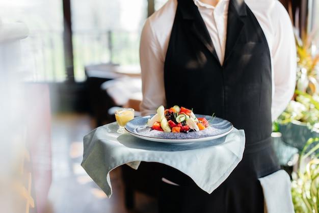 Молодой официант в стильной униформе стоит с изысканным блюдом на подносе возле стола в красивом ресторане крупным планом. ресторанная деятельность самого высокого уровня.