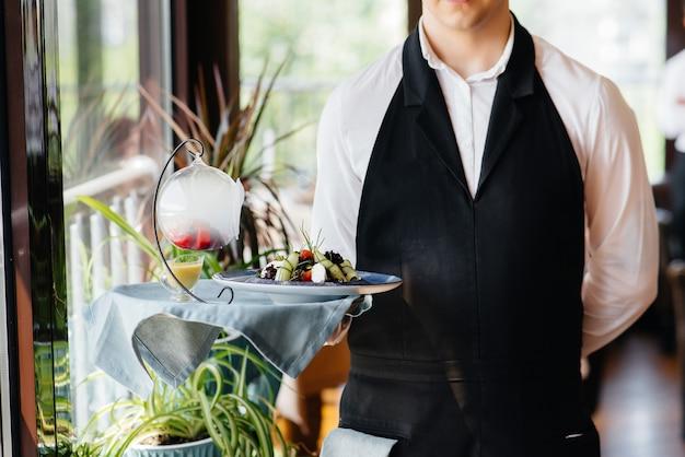 세련된 유니폼을 입은 젊은 웨이터가 아름다운 레스토랑 클로즈업에서 테이블 근처의 쟁반에 절묘한 요리를 들고 서 있습니다. 최고 수준의 레스토랑 활동.