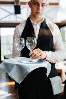 세련된 유니폼을 입은 젊은 웨이터가 아름다운 미식 레스토랑 클로즈업에서 테이블 근처의 쟁반에 안경을 들고 서 있습니다. 최고 수준의 레스토랑 활동.