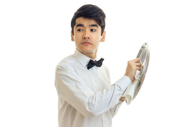 흰 셔츠에 젊은 웨이터가 흰 벽에 고립 된 식기의 측면과 측면 트레이를 찾습니다.