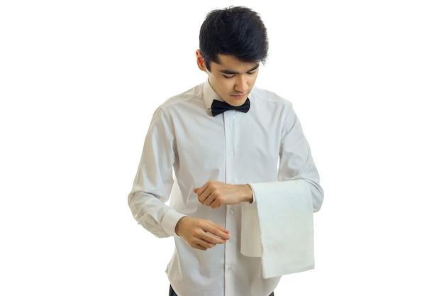 흰 셔츠에 젊은 웨이터가 머리를 기울이고 흰 벽에 고립 된 수건을 손에 유지합니다.