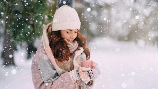 Молодая, тепло одетая женщина держит в руках чашку горячего напитка в снежный зимний день