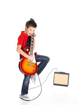 若い白人の少年が明るい感情でエレキギターを歌い、演奏し、白でアイソラタード