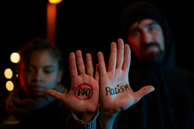 Молодой белый мужчина и молодая темнокожая женщина демонстрируют рукописное послание против расизма. серьезно смотрю в камеру