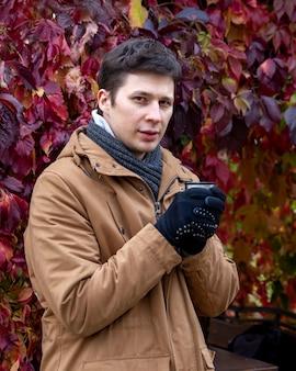 가을에 차 한 잔을 손에 들고 산책하는 젊은 백인 가을 초상화