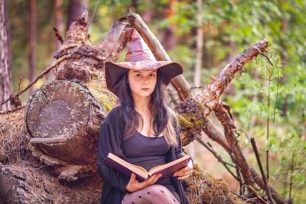 若い魔女が本を持って切り株の森の中に座っています。