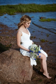 흰 드레스에 혼자 젊은 여자는 화창한 날씨에 여름에 그녀의 손에 꽃다발을 들고 해안에 돌에 앉아