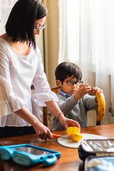 Молодая женщина и ребенок готовят фрукты утром на кухне