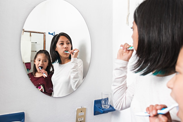 젊은 여성과 어린 소녀가 화장실 거울 앞에서 이를 닦는다