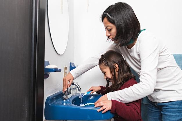 Молодая женщина и маленькая девочка моют зубные щетки в раковине ванной комнаты
