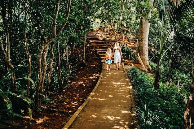 若い女性と小さな女の子が、モーリシャス島のシャマレル国立公園のエキゾチックな木々に沿った小道を歩きます。