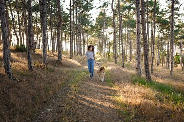 Летним вечером молодая женщина и пожилая собака гуляют по сельской местности. дама и ее верный друг с детства собака колли