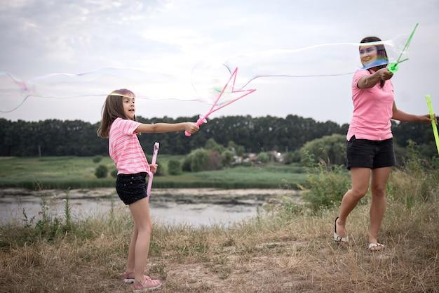 Молодая женщина и ее дочь запускают огромные мыльные пузыри на фоне красивой природы.