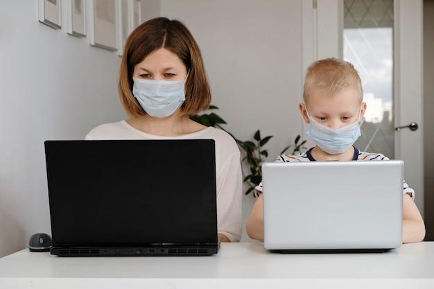 Молодая женщина и ее маленький сын сидят дома во время карантина и учатся в интернет-школе, используя компьютер.