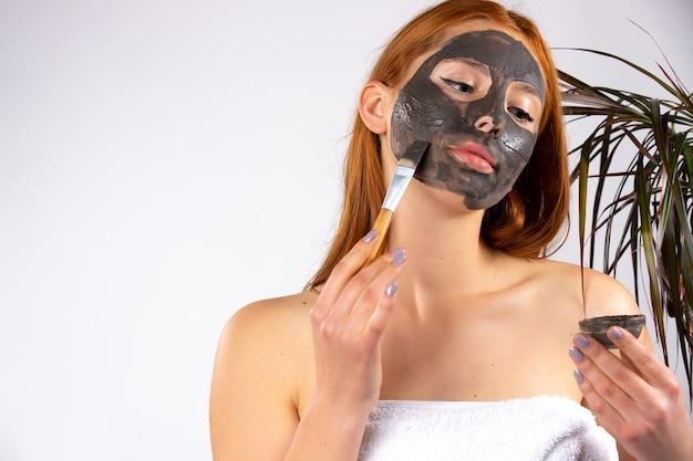 젊은 여자가 벽에 화장품 브러시 실내 꽃과 함께 그녀의 얼굴에 점토 마스크를 적용