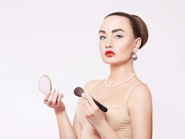 化粧をしている若い女性。
