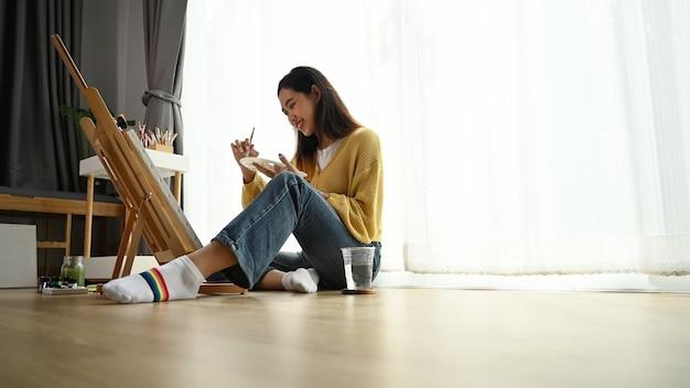 若い女性アーティストが家で絵を描いています