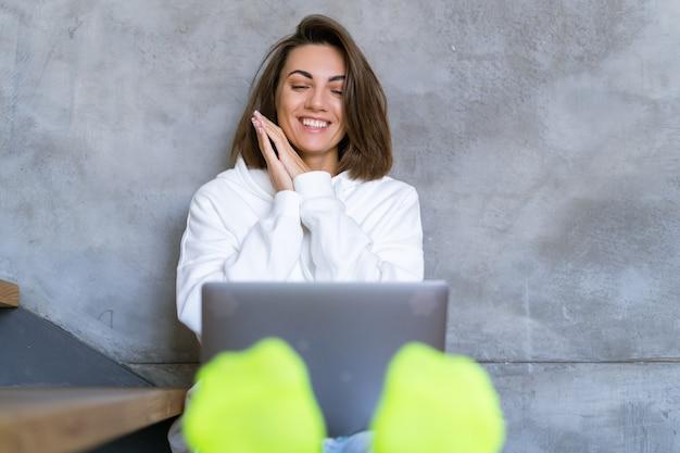 Молодая женщина дома в белой толстовке с капюшоном и джинсах сидит на лестнице с ноутбуком на коленях