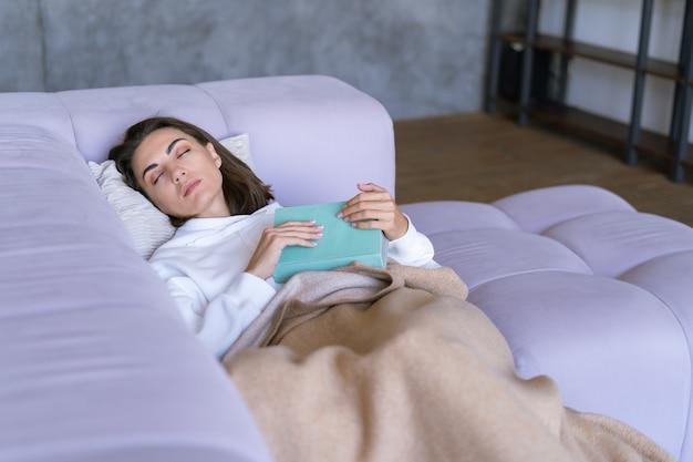 소파에 흰색 후드티를 입고 집에 있는 한 젊은 여성이 따뜻한 담요로 몸을 감싸고 잠들고 책을 읽습니다