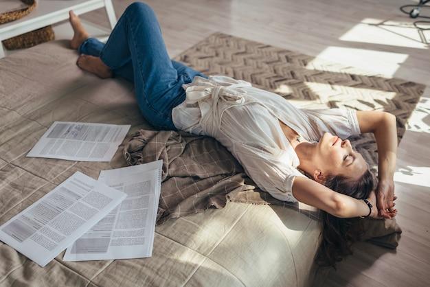 自宅の若い女性がベッドの上の書類の間に横たわって休んでいます。