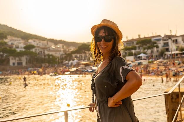팔라프루겔 마을의 타마리우 해안에서 석양을 바라보고 있는 젊은 여성. 지중해의 코스타 브라바 지로나