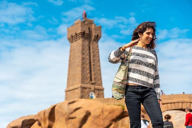 フランスのブルターニュにあるコートダモール県のペロスギレックの町にあるプルマナッコ港のミーンルス灯台にいる若い女性。