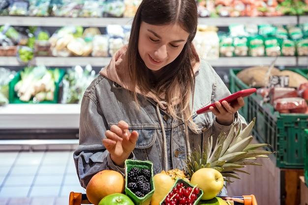 한 젊은 여성이 손에 휴대 전화를 들고 슈퍼마켓에서 식료품을 산다.