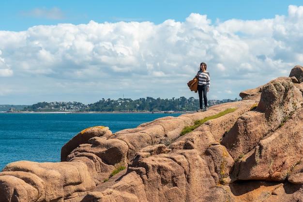 フランス、ブルターニュのコートダモール、ペロスギレックの町、プルマナッコ港の灯台ミーンルスの隣の海岸沿いの海沿いの若い女性。