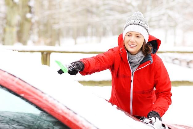 雪からフロントガラスを掃除する若い女性