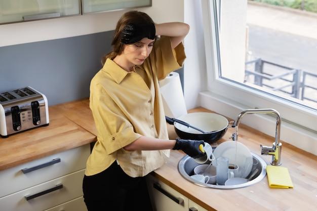若い女性が台所で掃除し、皿洗いをします。彼女は疲れていて、それをする必要があるという事実に満足していません。