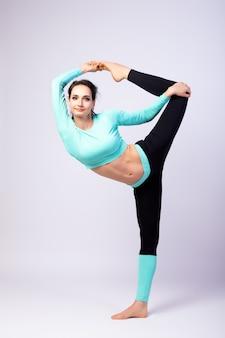 스튜디오에서 흰색 격리 된 배경에 젊은 여자 코치 스트레칭. 스포츠와 명상의 개념. 스트레칭 훈련