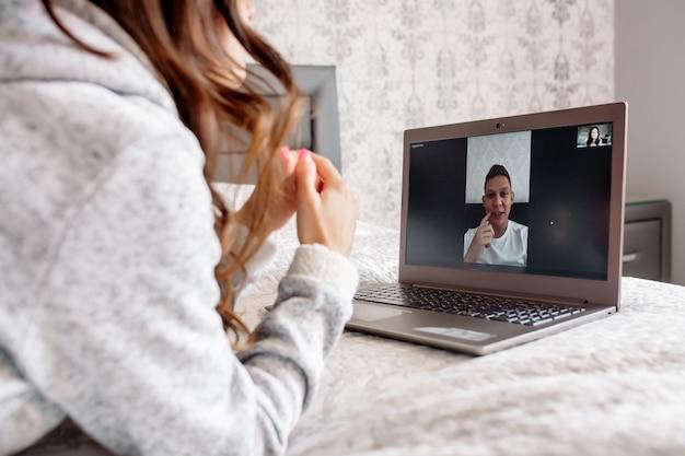 Молодая женщина общается с мужчиной по видеосвязи