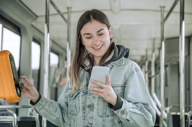 非接触型の若い女性が公共交通機関の料金を支払います。