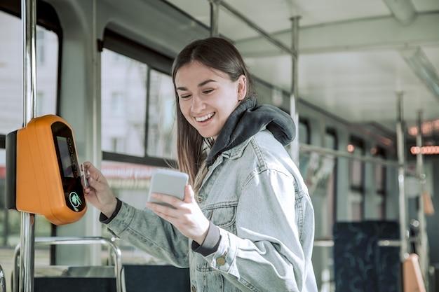 非接触型決済の若い女性が公共交通機関にお金を払う