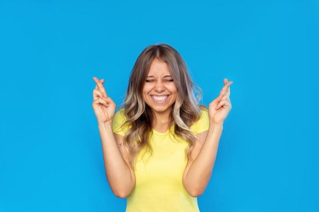 Молодая женщина скрещивает пальцы на удачу в ожидании результатов лотереи