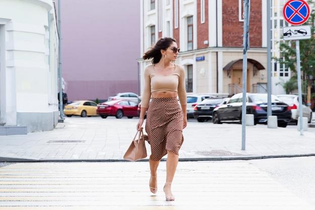 若い女性が街の道路を横断します。バッグと美しいスタイリッシュなブルネット。