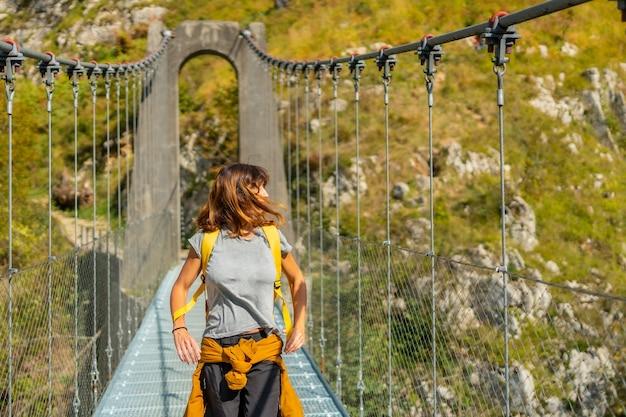 ラローのホルツァルテ吊橋を渡る若い女性。スペインのナバラとピレネーアトランティックの北にあるイラティの森またはジャングルで
