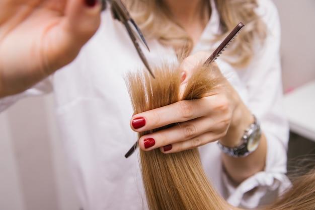Молодая женщина стрижет ножницами волосы. девушка расчесывает волосы. профессиональные средства по уходу за волосами. Premium Фотографии
