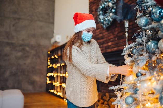 若い女性が医療用マスクでクリスマスツリーを飾る