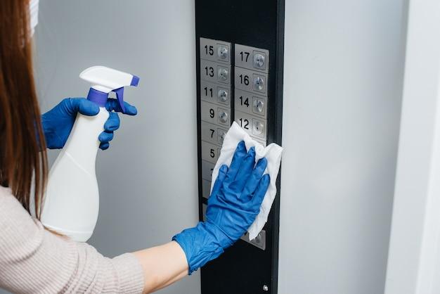 Молодая женщина дезинфицирует и чистит ключи в лифте во время глобальной пандемии. оставайся дома.