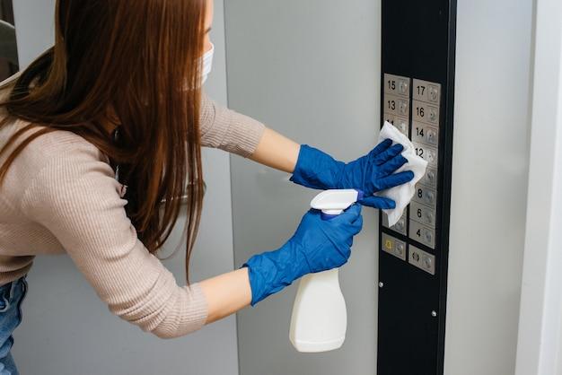 젊은 여성이 전염병이 발생한 동안 엘리베이터의 키를 소독하고 청소합니다.