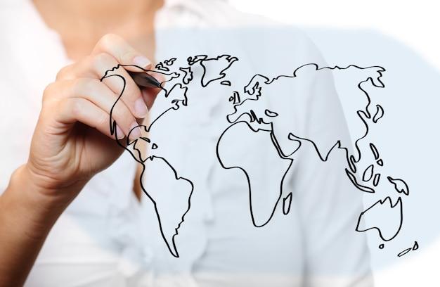 Молодая женщина рисует карту мира на белом фоне