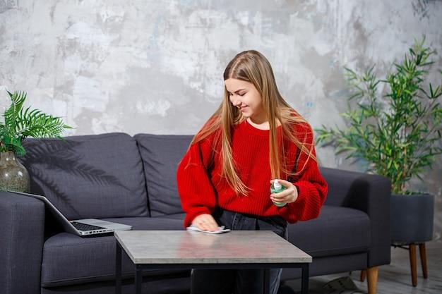 Молодая женщина в красном вязаном свитере убирает дома, вытирает пыль со стола.